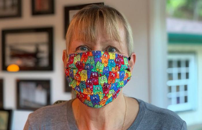 Woman wearing a multi-colored face mask that she made
