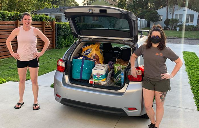 Emily Park and another woman standing next to a car with the hatchback up and filled with pet food donations