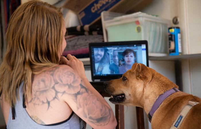 Woman next to Scooby the dog in front of a computer showing people doing a virtual adoption meet-and-greet