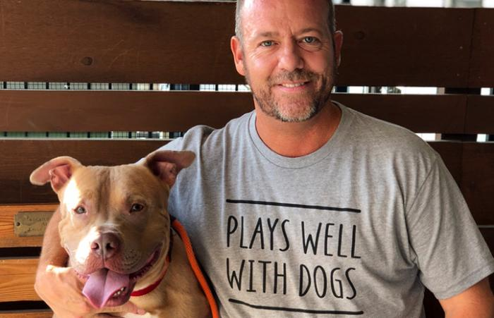 Scott Poore sitting next a pit bull terrier wearing a T-shirt that says, Plays well with dogs