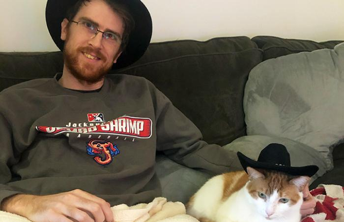 Levi the cat and his adopter sitting next to each other on a couch wearing matching black hats