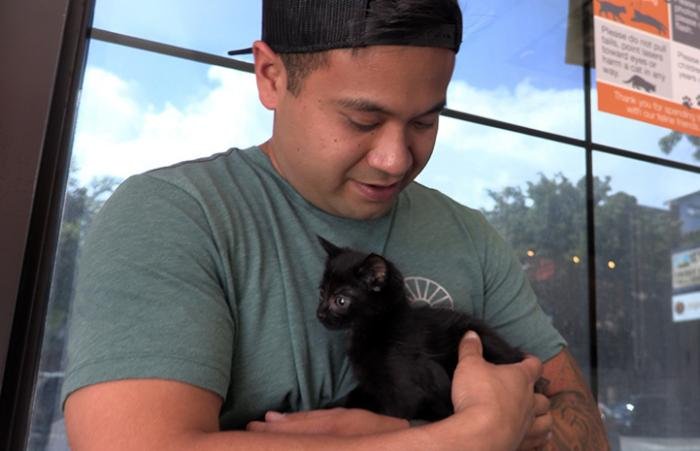 Volunteer Christian Ordonez cradling a small black kitten in his arms