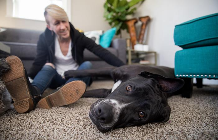 Woman sitting behind and petting a dog who is lying on the floor