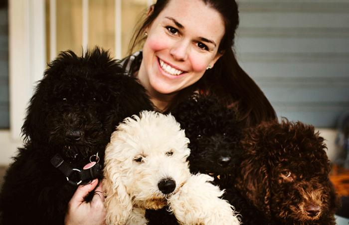 Georgia Cameron smiling and posing with four dogs