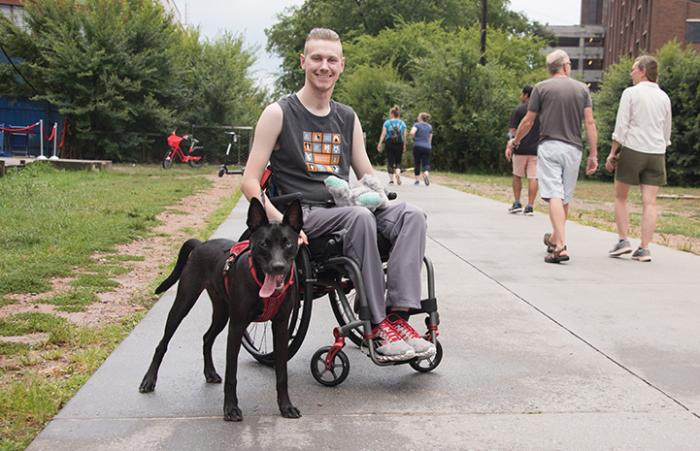 Man sitting in a wheelchair on a sidewalk with Bagel the dog standing next to him