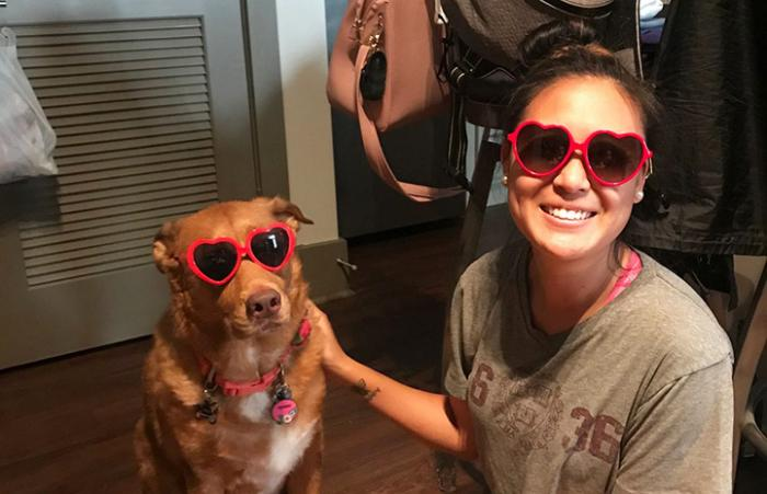 Smiling woman next to Sadie the dog, both wearing red, heart-shaped sunglasses