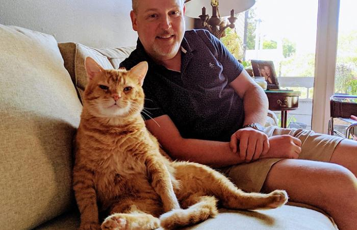 Steak the cat sitting on the couch next to a man in his new home