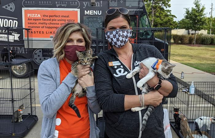Two women wearing masks and holding kittens at the Purrs & Pints drive-up adoption event