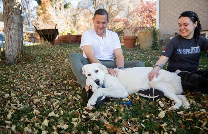 Great pyrenees dog Eddie lying outside in the lap of a man who is sitting next to a woma