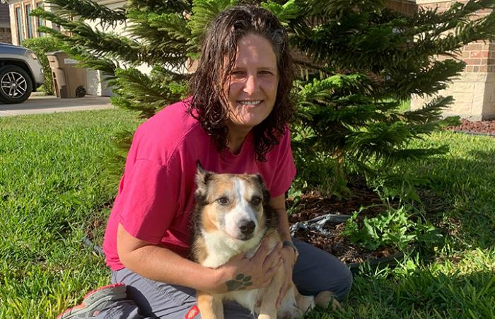 Woman sitting on the grass with Lovey the corgi in her lap