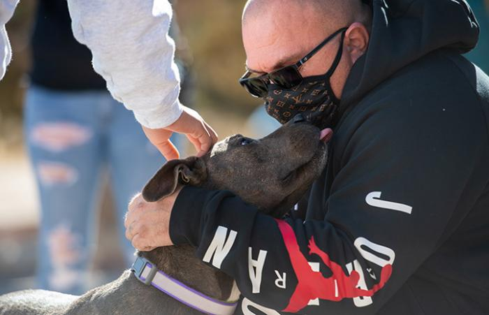 Stormy the dog reunited with his family and giving a kiss to a man in a mask