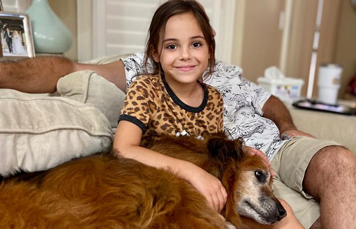 Young girl with senior dog lying in her lap