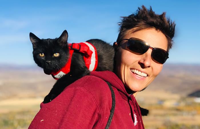 Rafa the black cat in a harness, lying on the shoulder of a smiling woman wearing sunglasses while outside