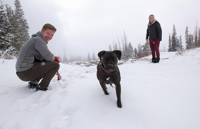 Dakota the dog in the snow with two people