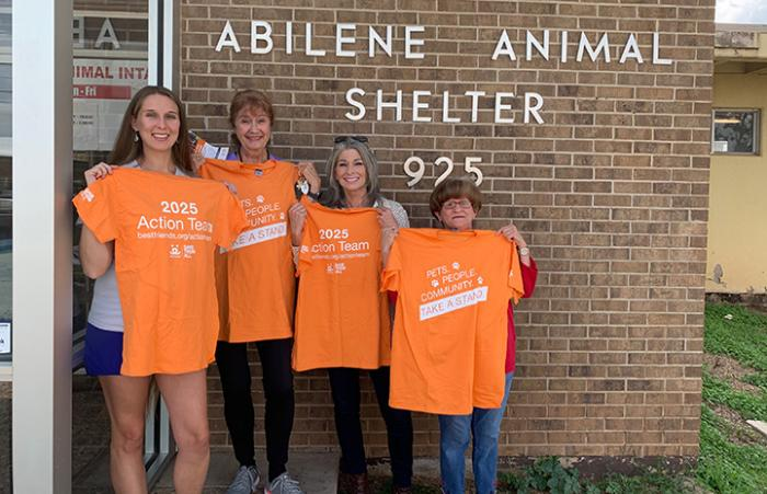Four people holding up orange Best Friends 2025 Action Team T-shirts, standing in front of Abilene Animal Shelter