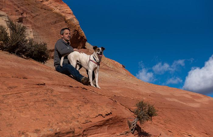 Man and a dog on a red cliff with a blue sky and white cloud behind them