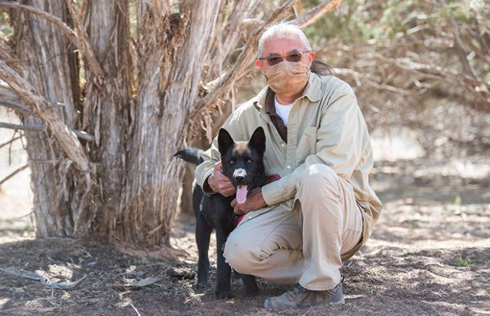 Keith Slim-Tolagai wearing a mask sitting under a tree with a black dog whose tongue is out