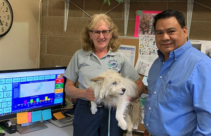 Two Madera County Animal Services employees standing next to a computer, one holding a small fluffy dog