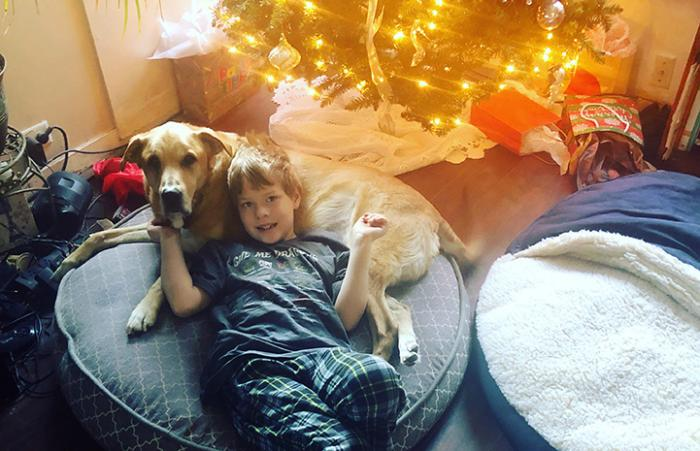 Ralph and a child lying together on a dog bed under a Christmas tree