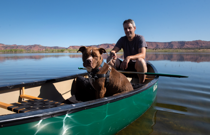 Lucci sitting in a canoe with a person