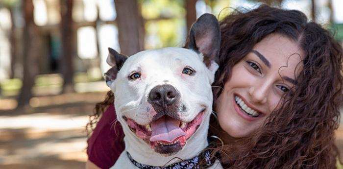 Smiling woman with her face next to a smiling dog