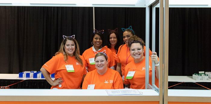 Group of women wearing Best Friends orange volunteer T-shirts and cat's ears at the National Conference
