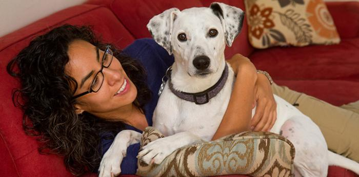 Woman lying on the couch with a white and black dog who she's hugging