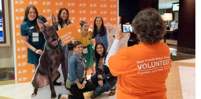 Best Friends National Conference volunteer taking a photo of a group of attendees in front of an orange backdrop, with a cutout