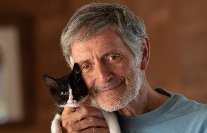 Gregory Castle, Co-Founder & CEO Emeritus, with tiny black and white kitten