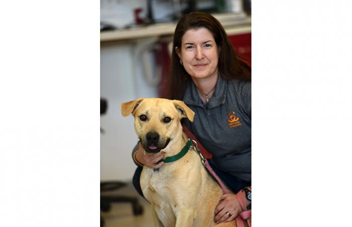 Dr. Erin Katribe, Medical Director with a yellow Lab dog