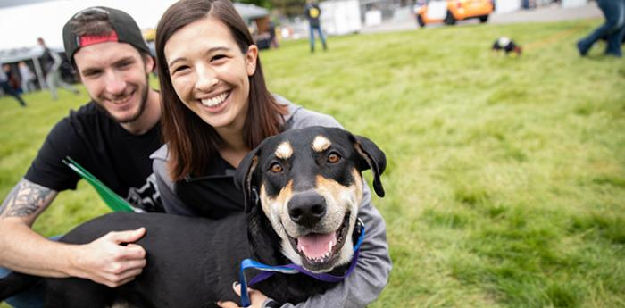 Smiling couple hugging a smiling black and tan dog at a Super Adoption event