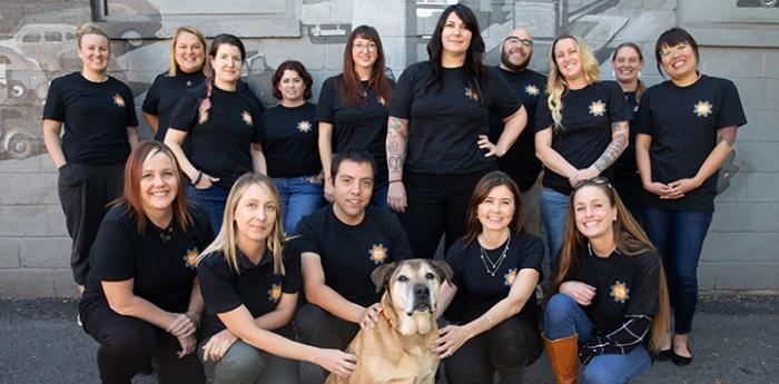Group of people who attended the executive leadership certification class posing with a dog