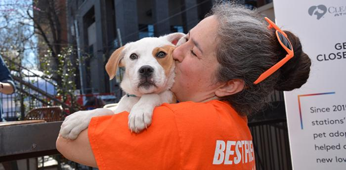 Best Friends volunteer holding and kissing a white and tan puppy