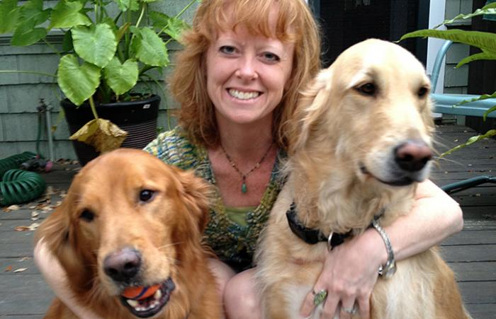 Kelly Morton posing with two golden retriever type dogs