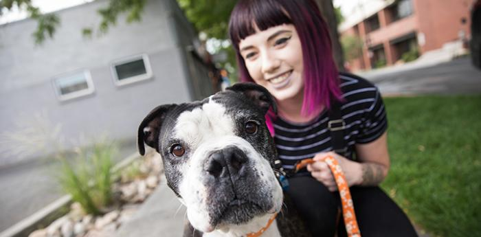 Black and white pit bull type dog in front of a smiling woman