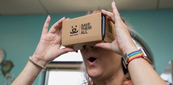 Woman holding a Best Friends branded cardboard virtual reality (VR) viewer