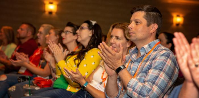 Group of people clapping at a Best Friends National Conference session