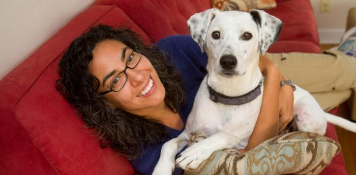 Woman and her white-and-black foster dog on red couch