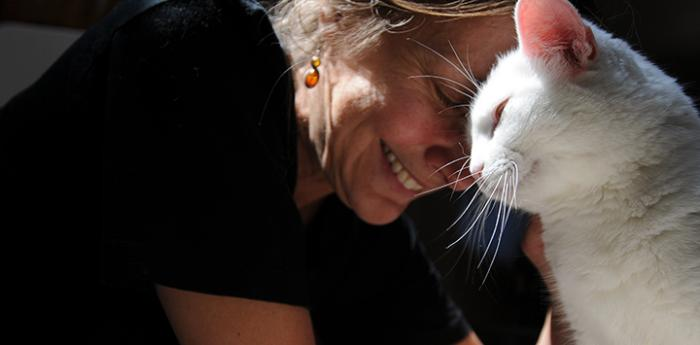 Smiling woman with her head against the head of a white cat
