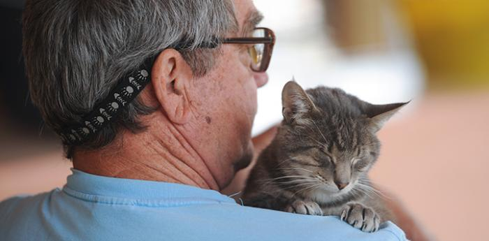 Man with his tabby cat. He has elected to make a planned gift of his retirement assets to help animals in need.
