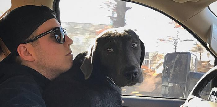 Alex Bowman in a car one of his dogs in his lap