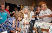 People gathering around a merchandise table at a Best Friends National Conference