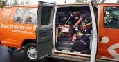 Cat Adoption Team (CAT) van with side doors open showing a person bending over a variety of kennels