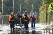 People maneuvering a boat through floodwaters in an effort to rescue animals