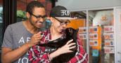Couple smiling and holding a black cat they're adopting