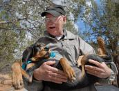 Dog and puppy volunteer Don Bain holding a puppy