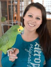 Kaila Huhtasaari of Pelkie, Michigan, holding a parrot during her parrot internship at Best Friends Animal Sanctuary