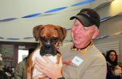 Ken Passarella at the Super Paw Showdown with the boxer dog he adopted named Oscar