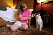 Cyndi Pearce with TJ the cat on a sleepover in a hotel room