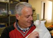 Rick Ducharme who is a huge proponent of TNR holding a white cat who has been spayed and vaccinated as part of a TNR program